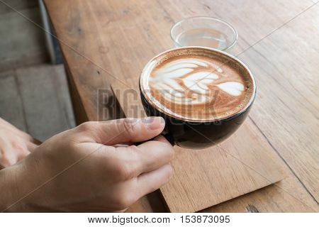 Hand on hot coffee latte stock photo