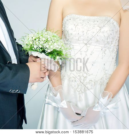 Wearing gloves and holding the bride and groom flowers, local close-up
