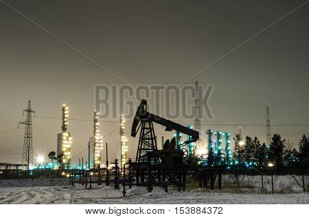 Oil pump and wellhead at the background of refinery by night. Oilfield during winter. Oil and gas industry.