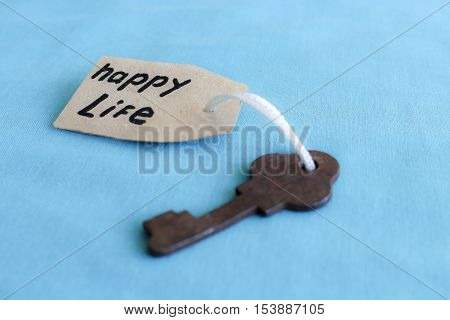 The concept of a happy life - the old key with a tag on turquoise background.