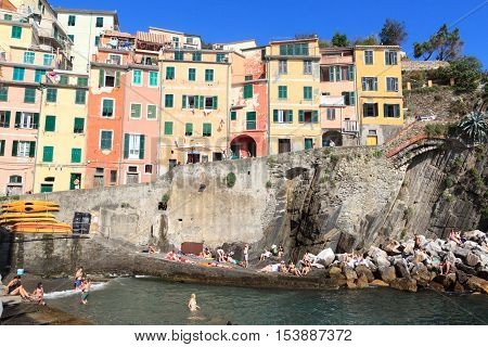 Riomaggiore, Italy - June 27, 2016: Village Riomaggiore with colorful houses and people bathing. Riomaggiore is one of the five villages in Cinque Terre and famous for its colorful houses.