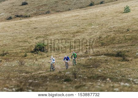 Privetnoye Russia - September 21 2016: three riders cyclists on a mountainbike ride valley in mountains during Crimean race mountainbike