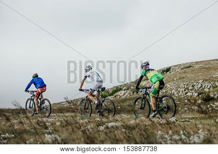 Privetnoye Russia - September 21 2016: three male riders cyclists mountenbike ride a mountain trail during Crimean race mountainbike