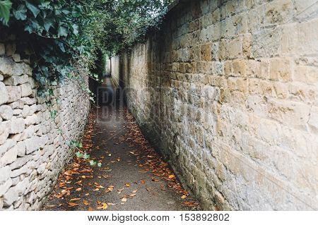 Old and dark alley with stone walls covered with plants in a village in the Cotswolds