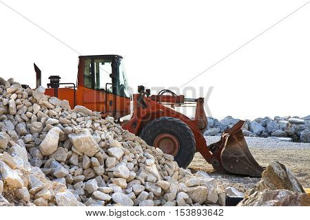 A digger builds a dam of white stones