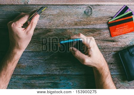 Man Hands holding credit card and using mobile phone. Online shopping online banking and online marketing. top view toning photo
