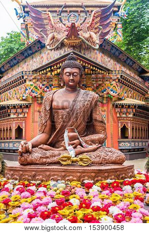 Idol of Magical Buddha god in meditation in front of a Bhutanese Pagoda with flowers in the foreground