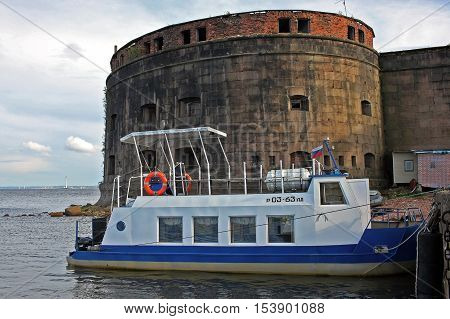 Kronstadt Russia - 10 July 2016: Tour boat moored at the Fort Alexander I or Plague Fort. Fort built in the years 1836-1845. In 1899-1917 the fort housed a research laboratory on plague and other bacterial diseases.