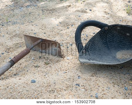 plastic hod and rake on sand in construction area