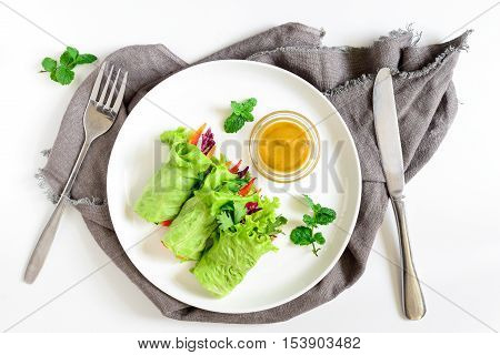 Lettuce vegetarian wraps or rolls stuffed with freshly chopped juicy vegetables and herbs served with sauce and decorated with fresh mint leaves view from above
