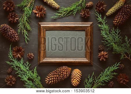 Christmas or New Year background dark moody board with a photo frame in the center with a blank space for greeting text decorated with various seasonal botanical elements such as fir branches and cones flat lay