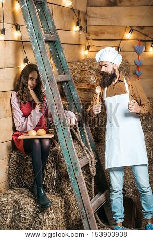Handsome man chef cook or baker with beard and moustache in hat with cute girl in apron near wooden ladder with buns on board on wood background
