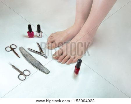 Feet need a pedicure. Legs with long nails and Tools for manicure(pedicure) on white background