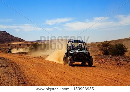 Merzouga Morocco - Feb 23 2016: front view on blue Polaris RZR 800 with it's pilots in Morocco desert near Merzouga. Merzouga is famous for its dunes the highest in Morocco.