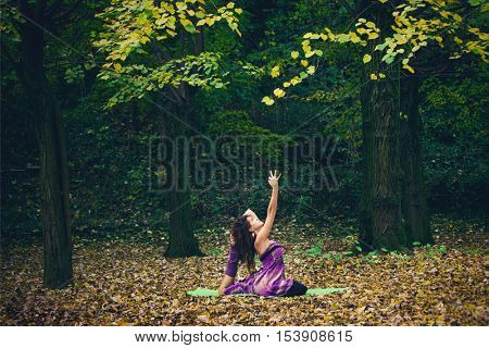 young woman practice yoga outdoor in autumn park day shot