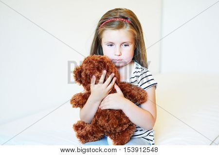 Depressed little girl hugging teddy bear at home