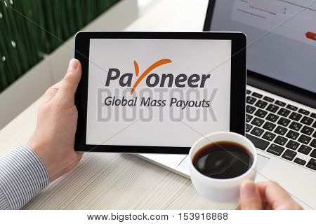 Alushta Russia - September 3 2016: Man holding a iPad Pro with payment system service Payoneer on the screen. iPad Pro was created and developed by the Apple inc.