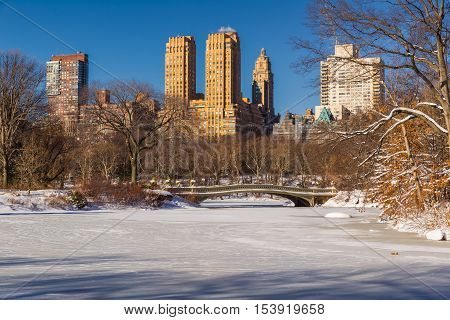 Frozen Central Park Lake with the Bow Bridge. Morning view of  Upper West Side buildings in Winter. Manhattan, New York City