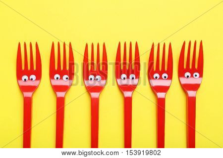 Red Plastic Forks With Googly Eyes On A Yellow Background