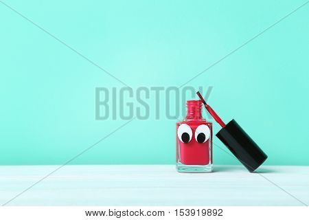 Bottle of nail polish with googly eyes on a green background