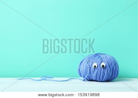 Ball Of Yarn With Googly Eyes On A Green Background