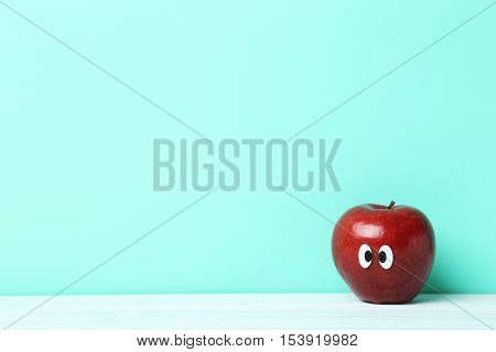 Red Apple With Googly Eyes On Green Background