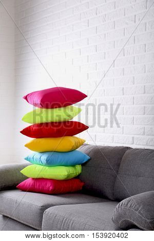 Colorful Pillows On Grey Sofa On A Brick Wall Background