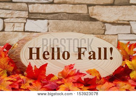 Hello Fall message Some fall leaves and wood plaque on weathered brick with text Hello Fall