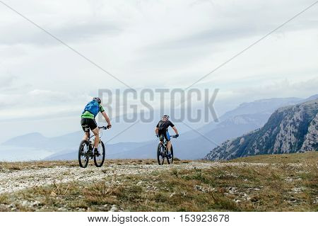 two men cyclists sports mountainbike rides on a mountain trail. Cycling competition mountain bike