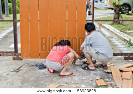 Blurred image of man and his daughter repairing the gate