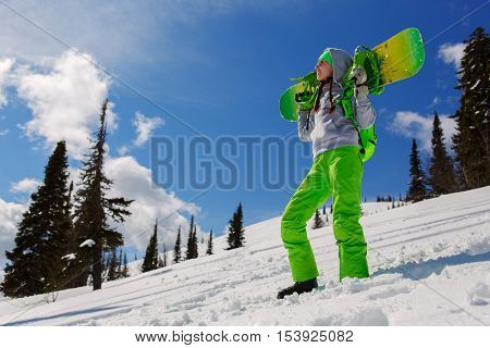 Girl snowboarder on a mountain slope with a snowboard on shoulders