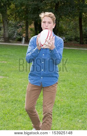 Teenager boy in the park playing with a rugby ball
