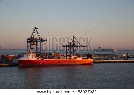 Massive orange freighter in the harbor of Seville Spain