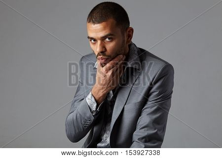 attractive young black man in gray blazer isolated on studio gray background
