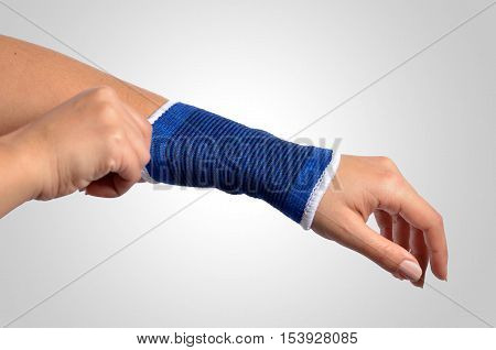 hand with a orthopedic wrist brace on grey background
