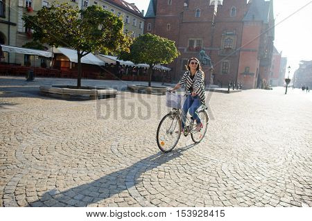 Dark-haired girl in sunglasses rides by bicycle on a paved pavement. Solar morning. Beautiful buildings of the ancient European city a monument green trees. Girl in a good mood she smiles.