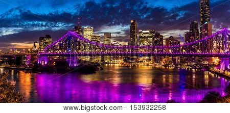 Vibrant night time panorama of Brisbane city with Story Bridge