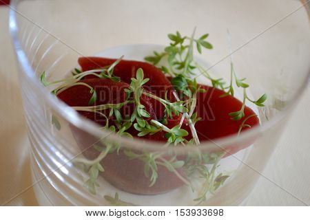 Creamy-fruity dessert in the glass garnished with cress