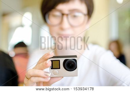 GoPro action camera which is holding a blurred happy girl with glasses