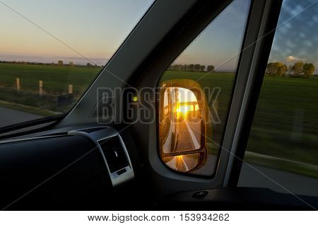 Side rear-view mirror in the evening on the road during sunset