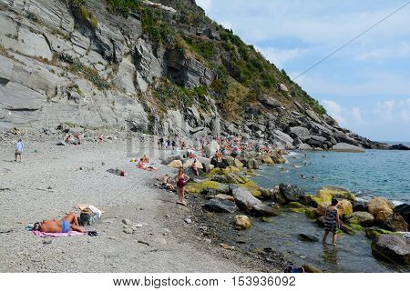 Vernazza Italy - September 4 2016: Unidentified people on rocky beach in Vernazza in Liguria Italy. One of five Cinque Terre cities (unesco world heritage)