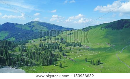mountainous landscape in Appenzell countryside in Switzerland, mountain meadows, woods, blue sky and white clouds
