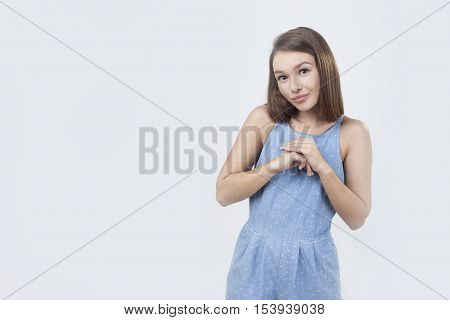 Shy woman in blue dress is standing with her arms together against gray background. Concept of shyness. Mock up