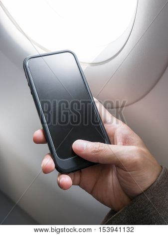 Hand holding blank and black cell phone beside an airplane window