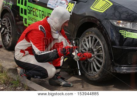Moscow Russia - Apr 18 2015: Unidentified driver changing car wheel during the Rally Masters Show 2015 at the Krylatskoye District.