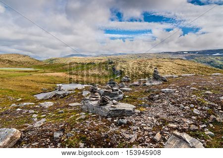 Mountain scenery - cairn - stone tower or pyramid on tourist path in Norway