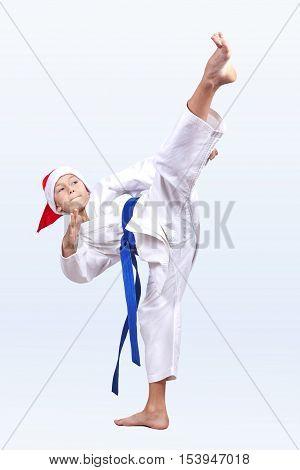High blow leg karateka is beating in a cap of Santa Claus