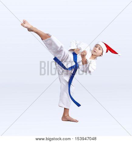 Roundhouse kick karate boy beats in a cap of Santa Claus