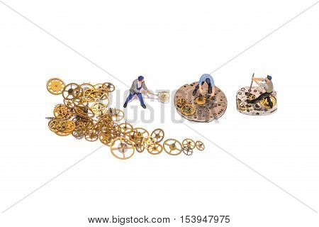 Miniature people repairing clockwork. Teamwork. Help in the work. Working employees. A pile of gear. Gears and clockwork isolated. Yellow cogs