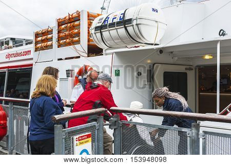 London, England - May 2016: Disabled woman embarks for the  Thames cruise